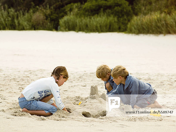 Siblings building sand castle on a beach.