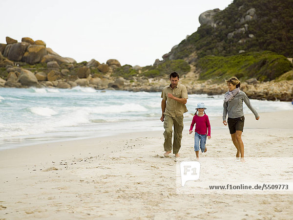 Parents running on the beach with their daughter.