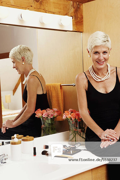 Portrait of a senior woman sitting in front of a mirror in the bathroom and smiling