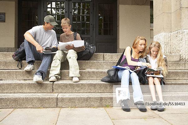 Zwei Mädchen und zwei Jungen auf der Schultreppe
