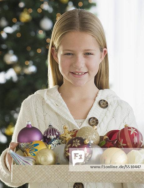 Girl holding Kiste Christbaumschmuck