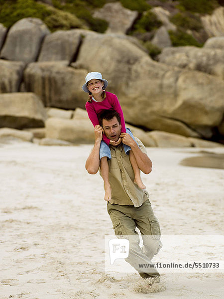 A father running with his daughter on his shoulders.