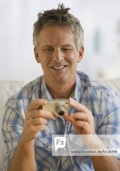 Man looking at digital camera
