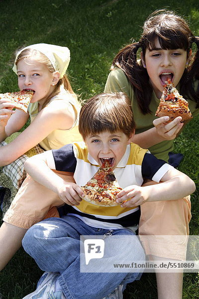 Three children eating pizza