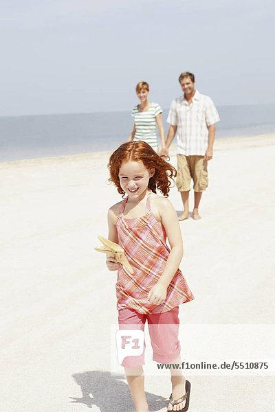 Paar und Tochter zu Fuß am Strand