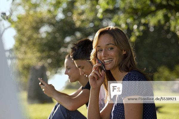 Drei jugendliche Freunde benutzen ihre Mobiltelefone