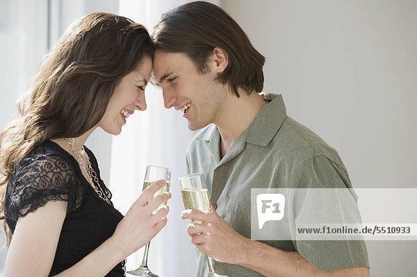Paar holding Champagne und berührt Stirn