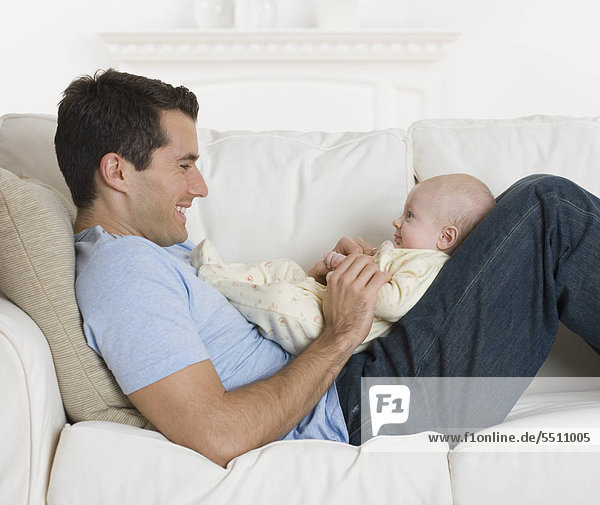 Vater Lächeln an Baby auf sofa