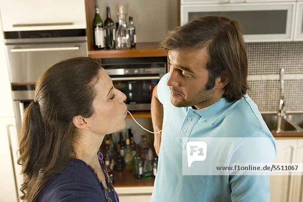 Couple having a strand of spaghetti together.