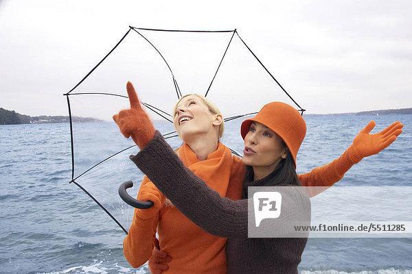 Zwei junge Frauen mit Regenschirm am Meer Zwei junge Frauen mit Regenschirm am Meer
