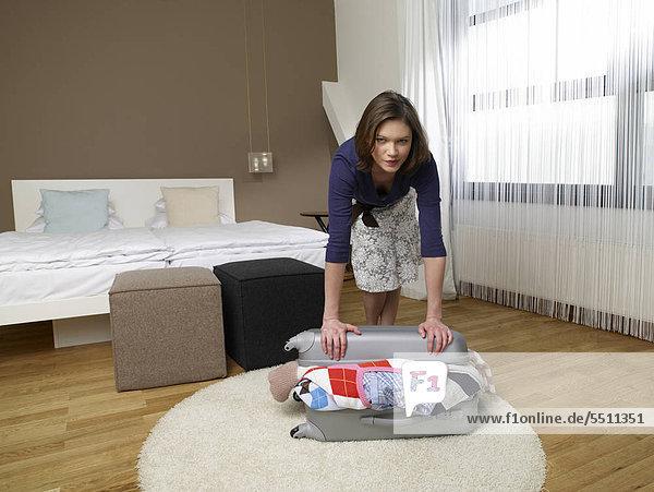 Junge Frau packt einen Koffer