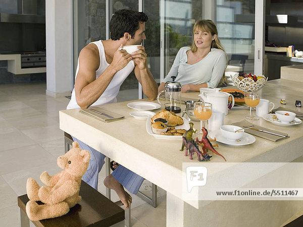 Junges Paar plaudert beim Frühstück