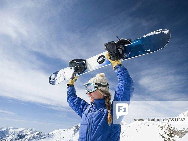 Woman holding Snowboard über Kopf