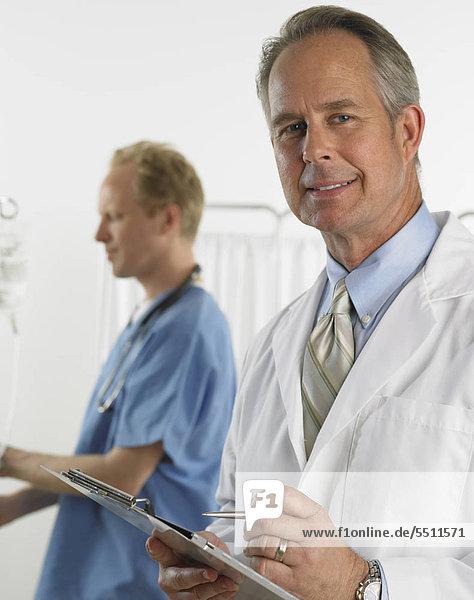 Männlichen Arzt lächelnd und holding Diagramm