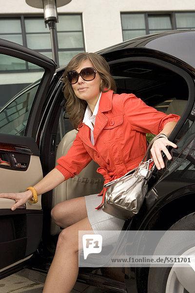 Junge Frau steigt aus dem Auto