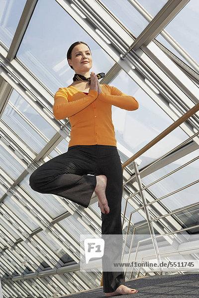 Junge Businessfrau beim Yoga im Büro