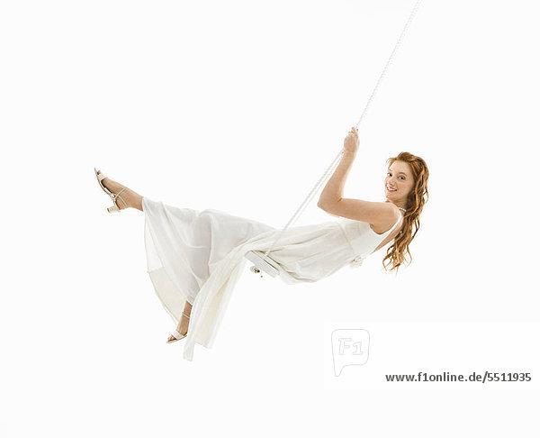 Caucasian Braut in Schaukel Schaukeln und Viewer betrachten.