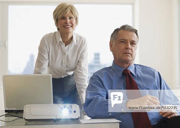 Leitende Geschäftsleute mit Projektor im Konferenzraum