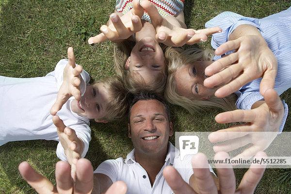 Familie mit zwei Kindern liegen auf dem Rücken