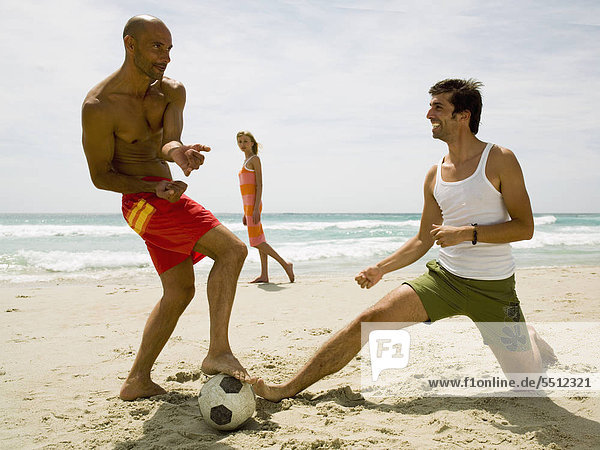 Woman looking at men playing football on the beach.