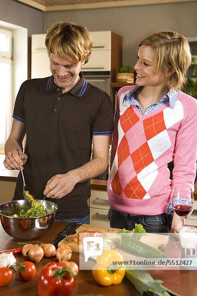 Junges Paar bereitet einen Salat zu