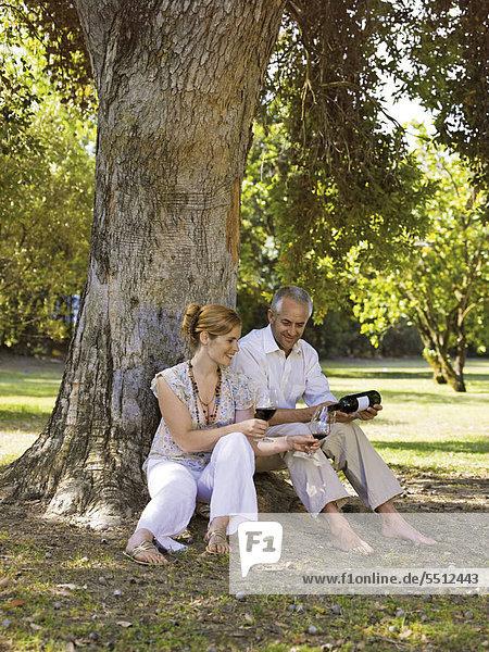 Ein Paar trinkt Wein unter einem Baum