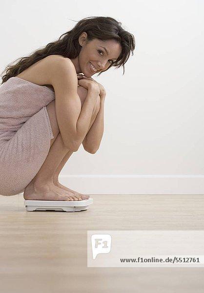 Waage - Messgerät hocken - Mensch Frau lächeln Badezimmer