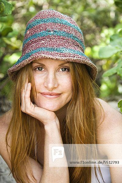 Portrait of pretty redheaded woman wearing hat.