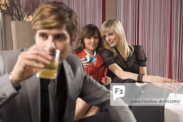 Mann in Bar  zwei Frauen im Hintergrund