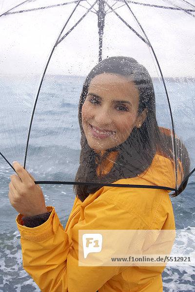 Junge Frau am Strand mit Regenschirm Junge Frau am Strand mit Regenschirm