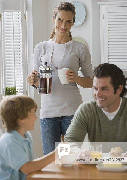 Mutter Lächeln an Vater und Sohn am Frühstückstisch