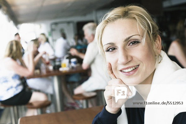 Porträt einer jungen Frau lächelnd mit der Hand auf ihr Kinn in einem restaurant