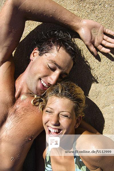 Glückliches Paar im Sand auf Maui  Hawaii Strand liegend lächelnd.