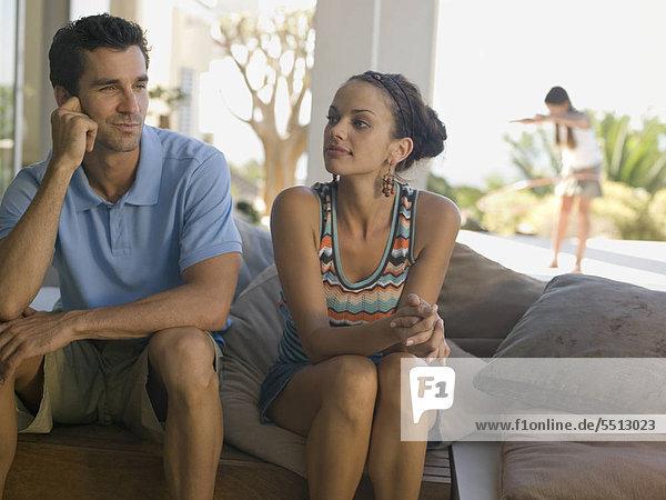Junges Paar in fröhlicher Stimmung  Tochter im Hintergrund
