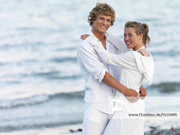 Junges paar umarmt am Strand