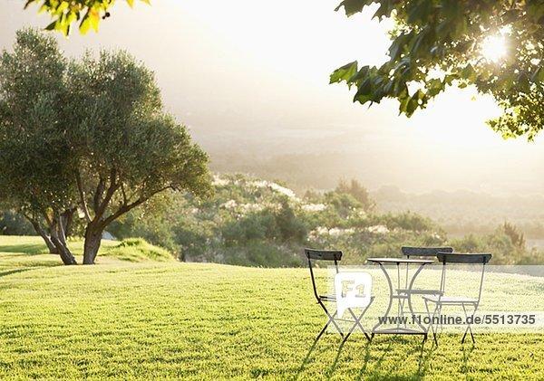 Tisch und Stühle auf einem sonnigen  idyllischen Feld