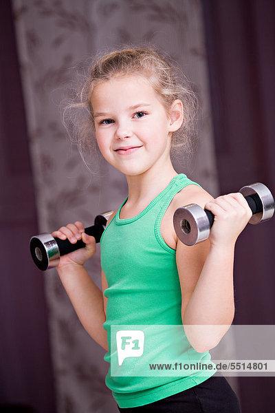 8-jähriges Mädchen trainiert mit kleinen Hanteln