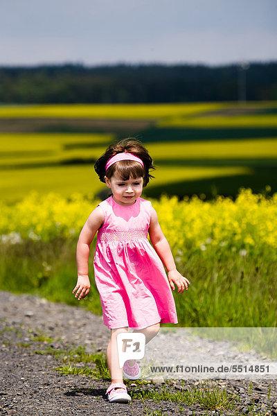 Kleines Mädchen spaziert auf Feldweg