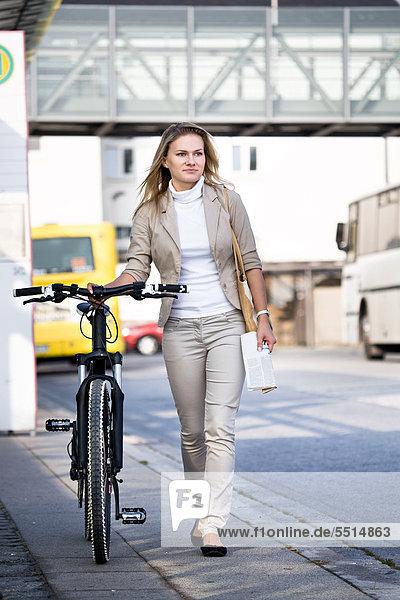 Junge Frau schiebt ihr Fahrrad  Sonneberg  Thüringen  Deutschland  Europa