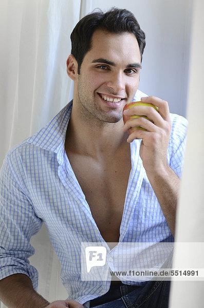 Junger Mann  auf Fensterbank sitzend und einen Apfel essend