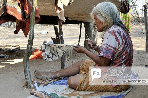 Indigene Frau  71 Jahre  vom Volk der Wichi  fertigt eine Tasche aus der Faser der Bromelie Chaguar (Bromelia hieronymi) an  Comunidad Santa Maria  Gran Chaco  Provinz Salta  Argentinien  Südamerika