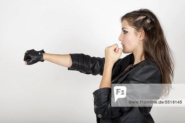 Junge Frau in Lederjacke  Boxhaltung  Kampfansage