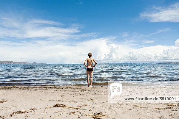 Eine junge Frau steht am Strand am Ufer des Titicaca-Sees  Lllachon  Capachica Halbinsel  bei Puno  Peru  Südamerika