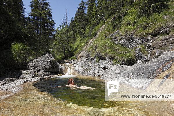 Frau badet in Gumpen am Schronbach  Schronbachtal  Gemeinde Jachenau  Isarwinkel  Oberbayern  Bayern  Deutschland  Europa