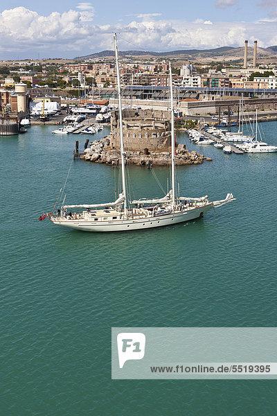 Segelyacht fährt vor historischer Kulisse in den Hafen von Civitavecchia  Rom  Italien  Europa