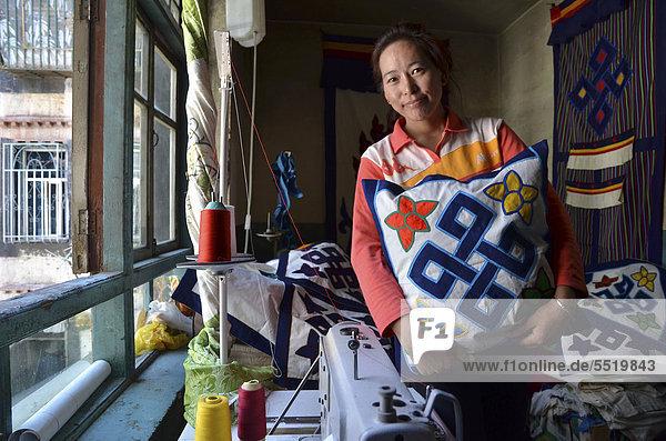 Tibetan handicrafts  dressmaker with Buddhist symbols on textiles  textile art  Tibet  Lhasa  China  Asia