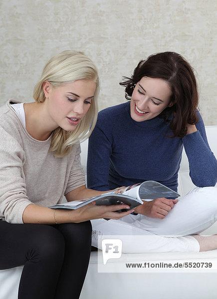 Zwei Freundinnen lesen eine Zeitschrift