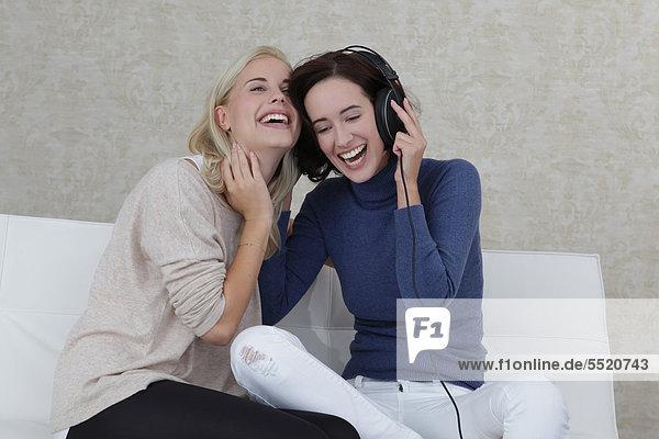 Zwei Freundinnen hören Musik auf dem Sofa