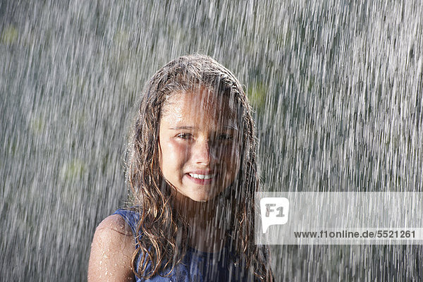Smiling girl playing in rain