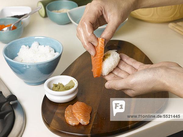 Frau bereitet Sushi bei Tisch zu